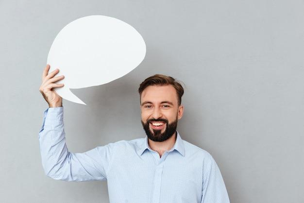 Heureux homme barbu dans des vêtements d'affaires tenant une bulle de dialogue vide