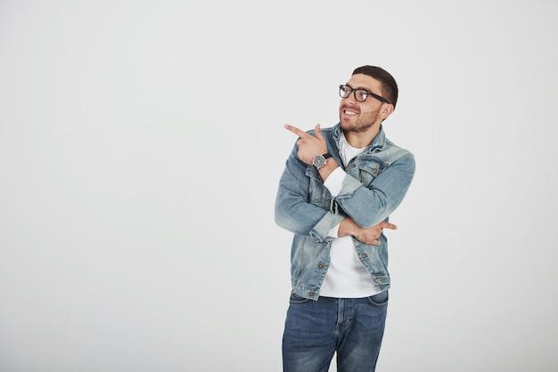 Heureux homme barbu excité à lunettes regardant la caméra avec le sourire et pointant loin