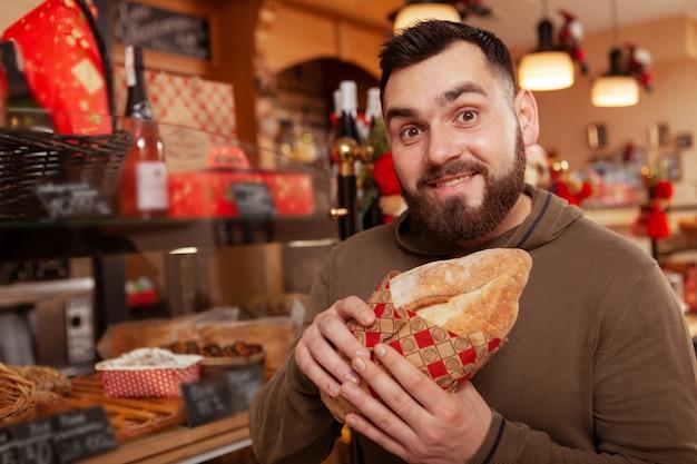 Heureux homme barbu faisant drôle de visage excité tout en achetant un délicieux pain frais, copiez l'espace
