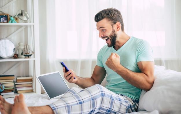 Heureux homme barbu fan heureux avec un ordinateur portable dans un grand lit blanc à la maison crie pendant la célébration