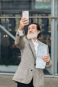 Heureux homme barbu gris senior faire un selfie avec carte sur le fond de l'aéroport