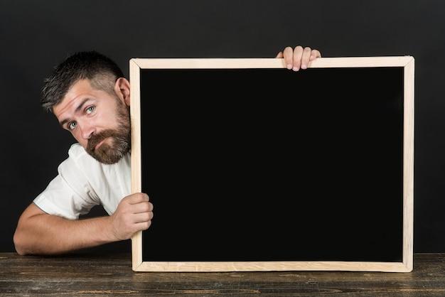Heureux homme barbu, homme d'affaires, enseignant, professeur, érudit assis à table tenir le tableau. l'homme en chemise blanche tient un tableau noir, une bannière, un panneau d'affichage vierge. retour à l'école. notion d'école. espace de copie.