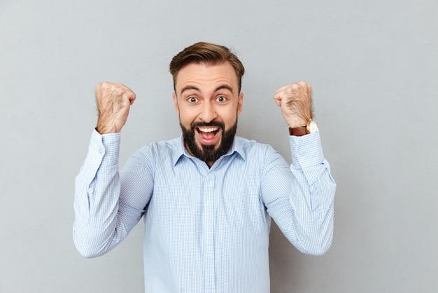 Heureux homme barbu hurlant dans des vêtements d'affaires regardant la caméra