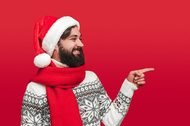 Heureux homme barbu en pull tricoté chaud et bonnet de noel