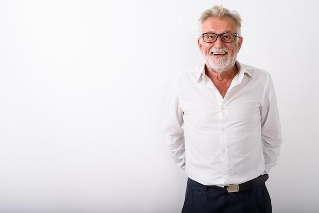 Heureux homme barbu senior souriant avec les mains derrière le dos tout en portant des lunettes sur blanc