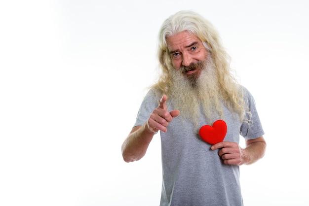Heureux homme barbu senior souriant et pointant vers l'avant