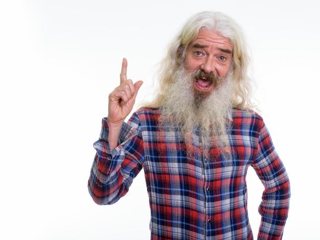 Heureux homme barbu senior souriant tout en pointant vers le haut
