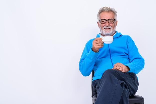Heureux homme barbu senior souriant tout en tenant une tasse de café et assis sur une chaise prête pour la salle de sport sur blanc