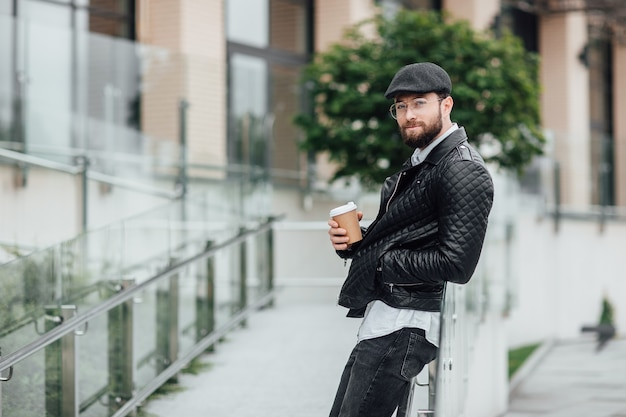 Heureux homme barbu, sérieux et élégant marchant dans les rues de la ville près du centre de bureaux moderne avec café