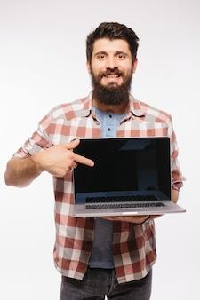 Heureux homme barbu souriant tenant un ordinateur portable à écran blanc isolé sur un mur blanc
