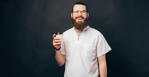 Heureux homme barbu souriant tient une tasse à emporter.