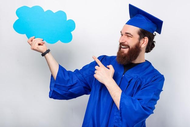 Heureux homme barbu vêtu d'une robe de graduation bleue tient une bulle de nuage.