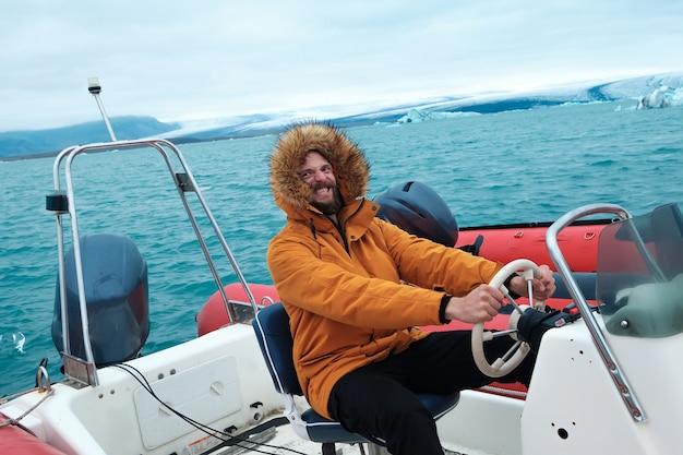Heureux homme sur un bateau sur le lagon glacé de joculsarlon, islande. célèbre lagune de glace islandaise, où la glace descend pour atteindre l'océan. les gens marchent et prennent le bateau pour enquêter sur une destination célèbre.