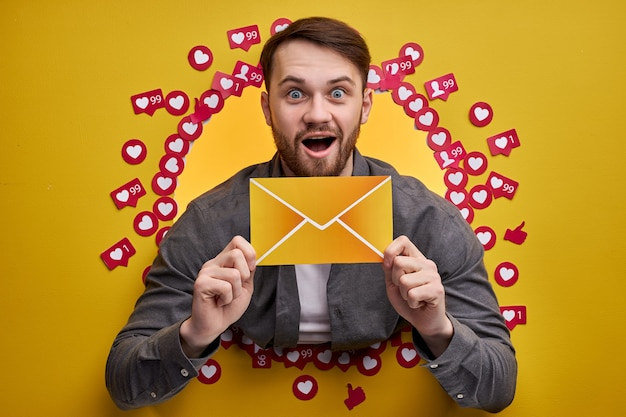 Heureux homme bénéficiant de commentaires positifs, veulent plus d'abonnés et de messages, tenant une lettre dans les mains.
