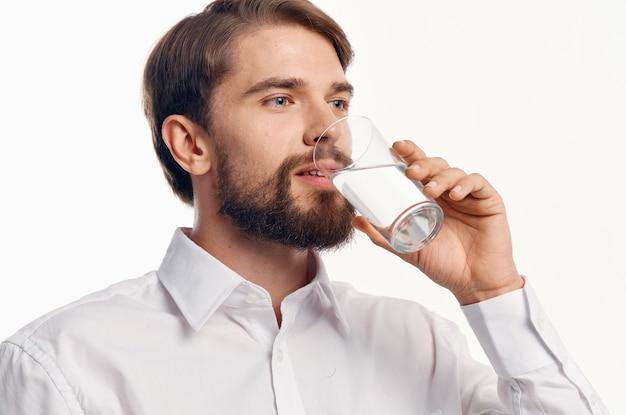 Heureux homme boit de l'eau dans un verre sur un modèle de portrait de chemise blanche fond clair