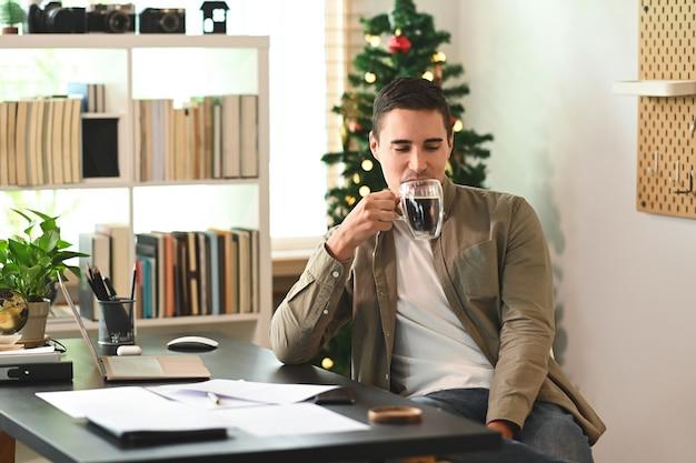 Heureux homme buvant du café alors qu'il était assis au bureau à domicile.