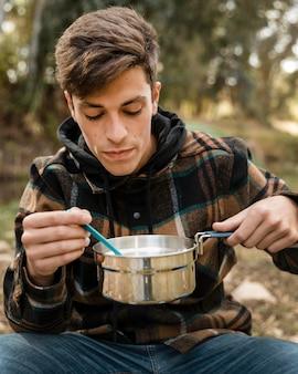 Heureux homme de camping dans la forêt de manger du pot