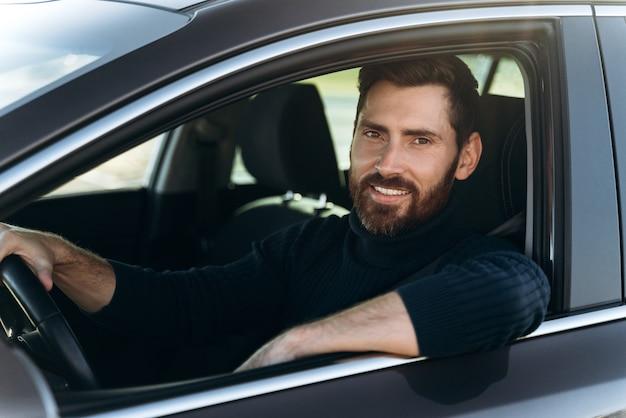 Heureux homme caucasien assis et regardant la fenêtre tout en ayant une longue route en voiture. personnes occupées et concept de transport