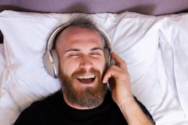 Heureux homme caucasien sur le lit portant un casque écouter profiter de sa musique préférée, se reposer seul, danser.