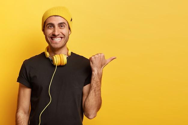 Heureux homme caucasien positif avec sourire à pleines dents, pointe le pouce sur un espace vide, élément de promesse