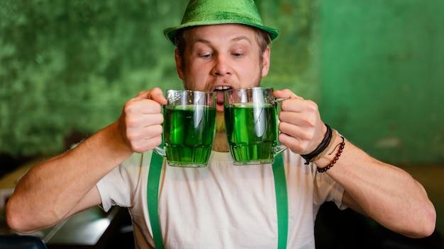 Heureux homme célébrant st. patrick's day avec boissons au bar