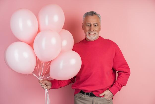 Heureux homme célébrant la tenue de ballons roses