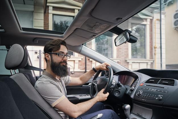 Heureux homme charismatique au volant d'une voiture
