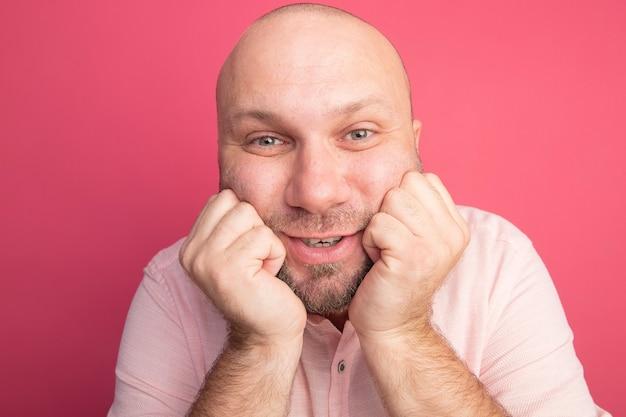 Heureux homme chauve d'âge moyen portant un t-shirt rose mettant les mains sur le menton isolé sur rose