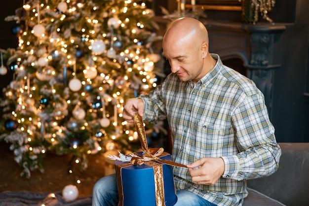 Heureux homme chauve en chemise ouvre un cadeau de noël alors qu'il est assis sur le canapé dans le contexte...