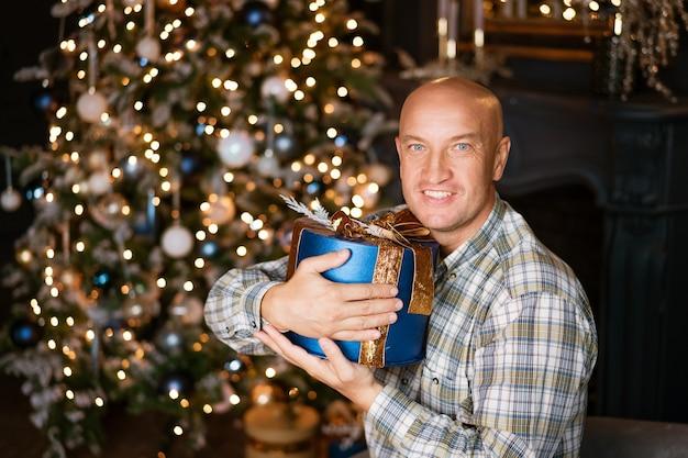 Heureux homme chauve dans une chemise tenant une boîte bleue avec un cadeau sur le fond d'un arbre de noël