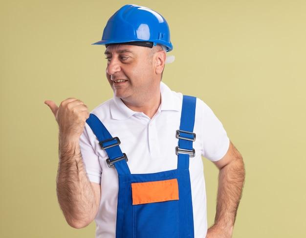 Heureux homme constructeur adulte en uniforme regarde et points sur le côté isolé sur mur vert olive