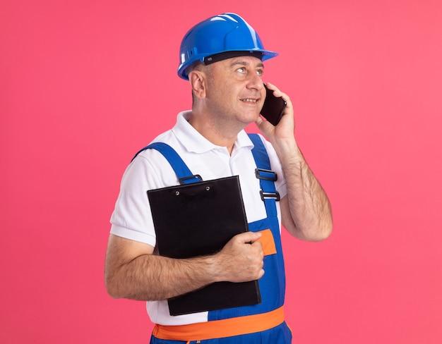 Heureux homme constructeur adulte en uniforme tient le presse-papiers et parle au téléphone à côté isolé sur mur rose