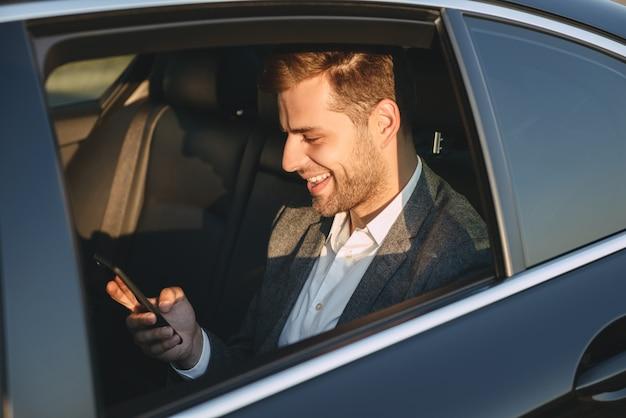 Heureux homme en costume classique tenant et utilisant un téléphone portable, tout en étant assis dans une voiture de classe affaires