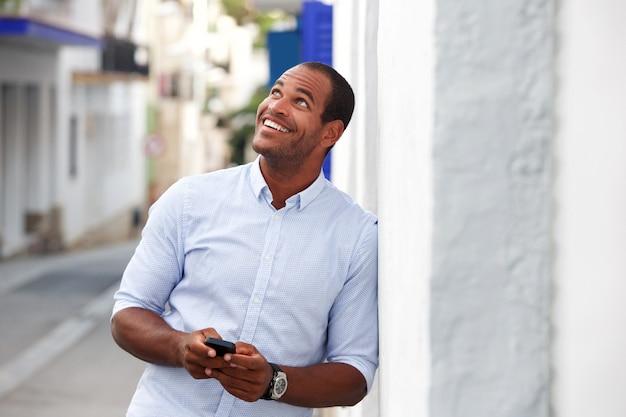 Heureux homme debout dehors dans la rue avec téléphone portable