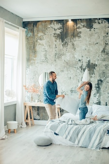 Heureux homme debout devant un lit et riant pendant la bataille d'oreillers avec une petite amie