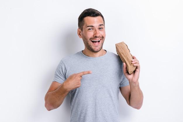 Heureux homme debout sur fond de studio blanc et pointant sur le bois de chauffage tout en le tenant sur son épaule. image studio, isolé sur fond blanc