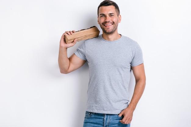 Heureux homme debout sur fond de studio blanc et tenant un bois de chauffage sur son épaule. image studio, isolé sur fond blanc