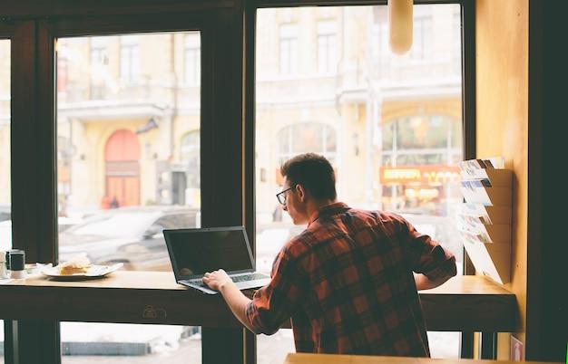 Heureux homme décontracté à l'aide d'un ordinateur portable au café