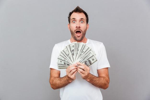 Heureux homme décontracté tenant des factures de dollars américains sur fond gris
