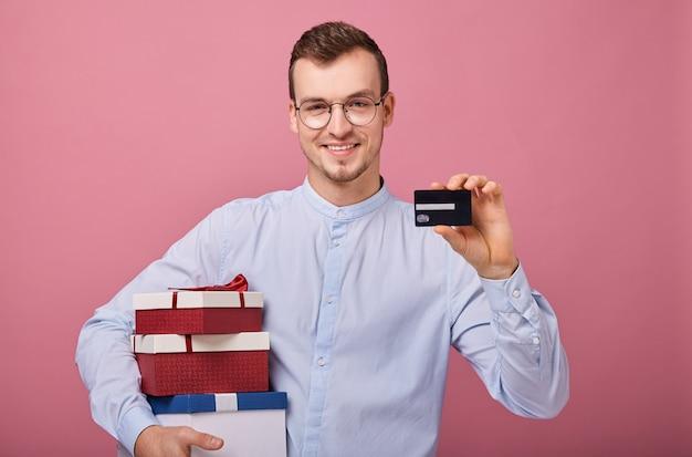 Heureux homme détient trois cadeaux colorés dans des boîtes avec couvercle et arc dans ses mains