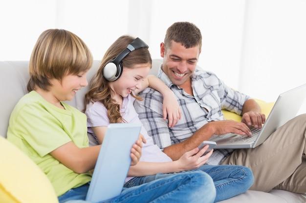 Heureux homme avec des enfants qui utilisent des technologies