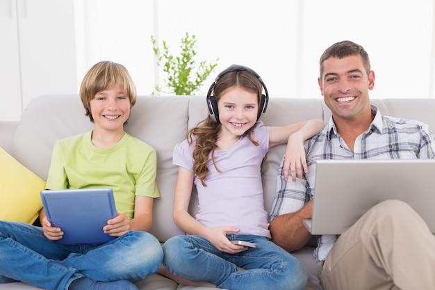 Heureux homme avec des enfants en utilisant des technologies sur le canapé