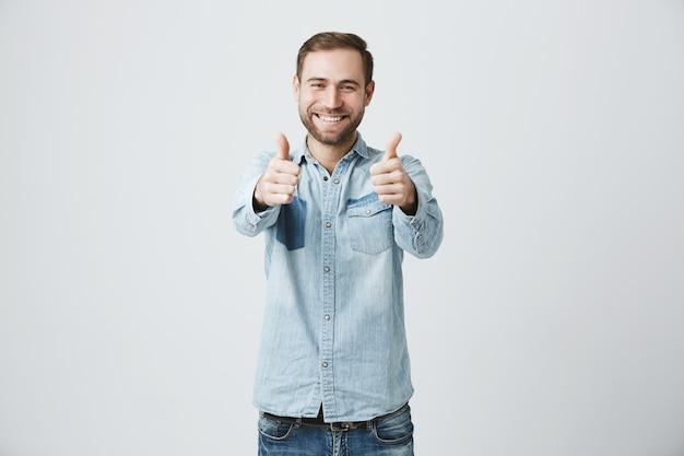 Heureux homme excité avec barbe montrant le geste des pouces vers le haut,