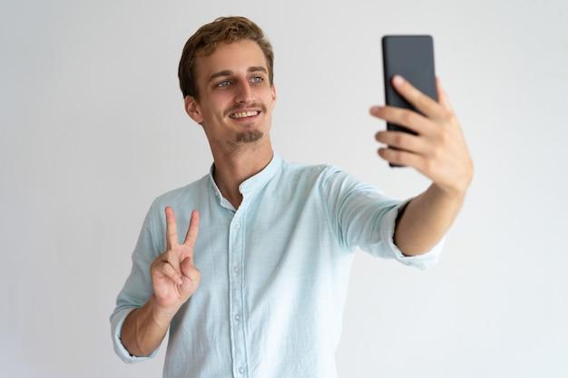 Heureux homme excité montrant signe de paix en prenant selfie.