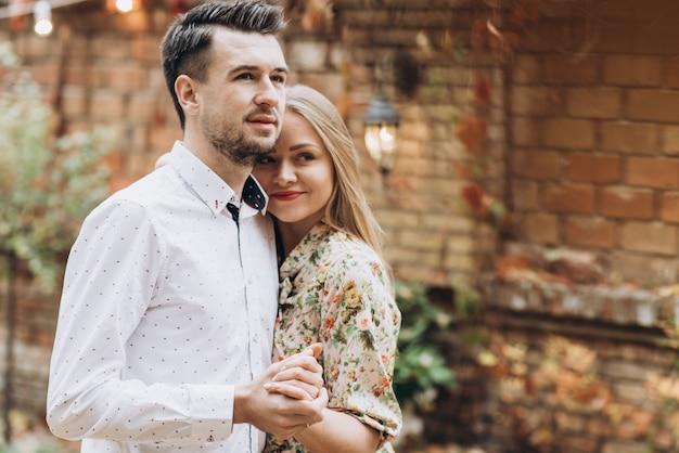 Heureux homme et femme amoureux datant de la rue d'automne. heureux couple de deux embrassant pendant la journée confortable dans le parc. concept de mode de vie
