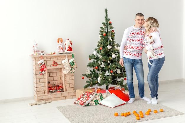 Heureux homme et femme à l'arbre de noël à la maison