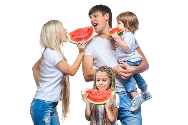 Heureux homme et femme avec deux enfants va manger de la pastèque isolé sur blanc