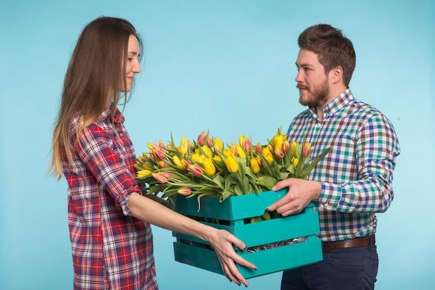 Heureux homme et femme fleuristes tenant la boîte avec des tulipes et riant sur fond bleu