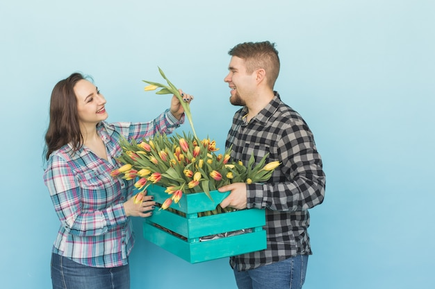 Heureux homme et femme fleuristes tenant boîte avec des tulipes et rire sur fond bleu