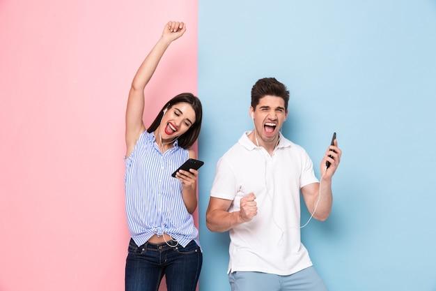Heureux homme et femme portant des écouteurs, écouter de la musique sur les smartphones, isolé sur un mur coloré